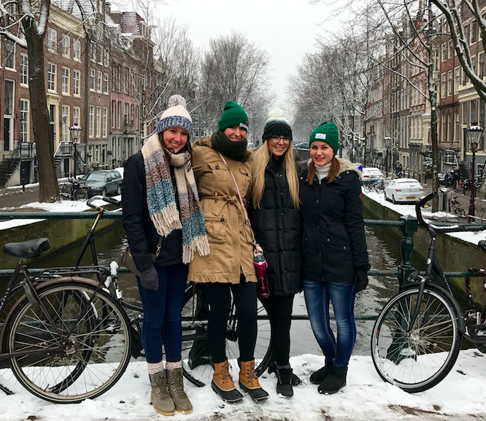 Posing for a picture by one of Amsterdam's many canals with my smiling, frozen, travel buddies